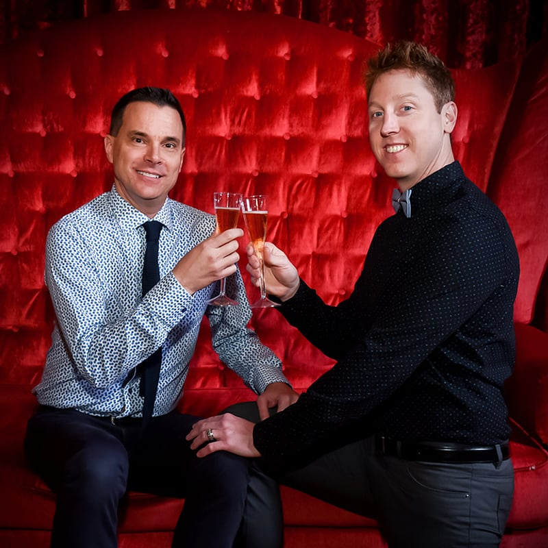 Two men toasting with glass of champagne at the Zumanity Wedding Experience